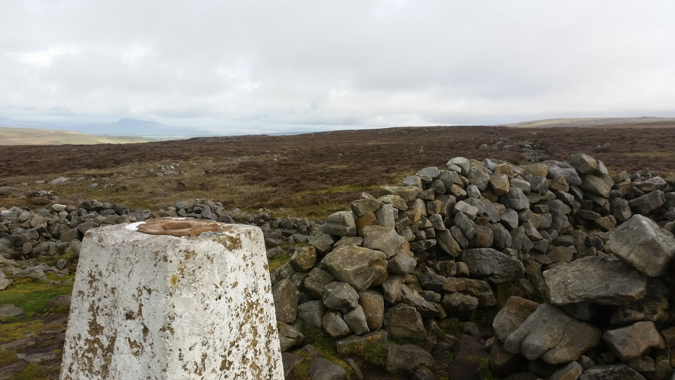 """Standing next to a survey marker, the view over moorland with hills in the distance"""